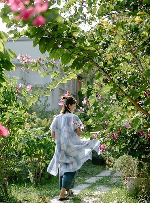 młoda kobieta w ogrodzie wiejskim wśród krzewów róż