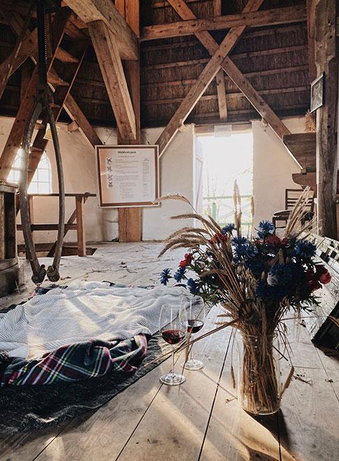 wnętrze wiejskiej chaty z wysokim stropem z drewna z bukietem polynch kwiatów w wazonie