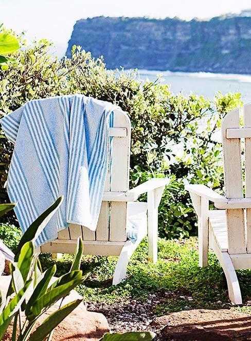 Biały fotel gordowy z drewna na trawie z widokiem na morze