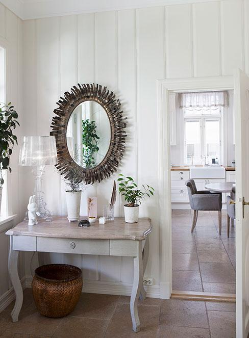 przedpokój z bieloną konsolą w białym drewnianym domu w stylu rustykalnym