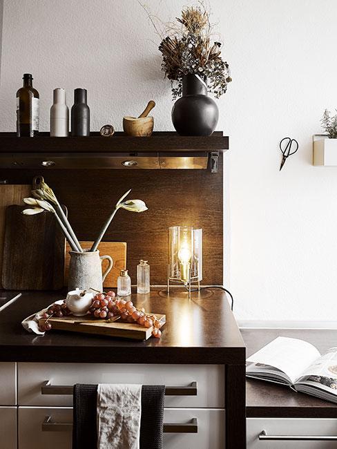 Kuchenka z ciemnego drewna i wazonem z kwiatami z kamionki w stylu rustykalnym