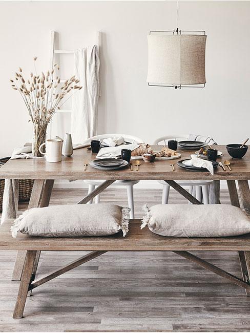 rustykalna jadalnia z drewnianym stołem i ławkami i beżowymi poduszkami z lnu