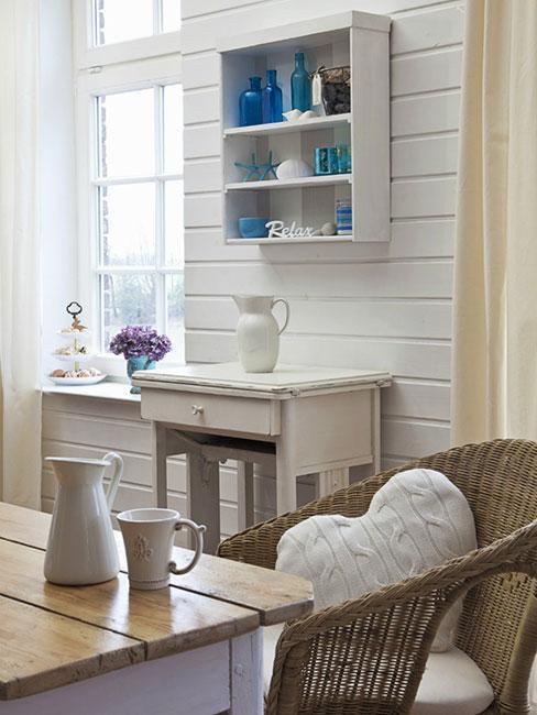 Kuchnia z białymi drewnainymi meblami i fotelem z wikliny w stylu rustykalnym