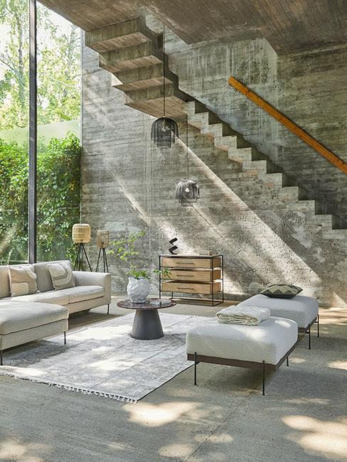 duży salon w szarym lofcie z betonu z beżową sofą i dekoracjami boho
