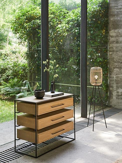 nowoczesna komoda z drewnaianymi szufladami w metalowej ramie przy dużym oknie w lofcie