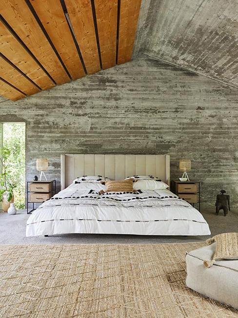 Duże łóżko w sypialni z szarego betonu w lofcie