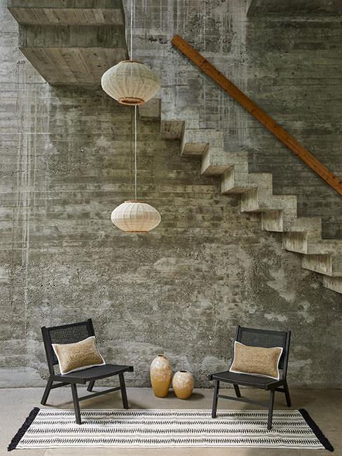 kącik kawowoy z dwoma czarnymi ażurowymi fotelami w lofcie z szarego betonu