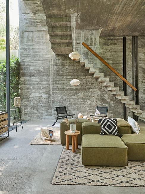 salon w lofcie z szarego betonu z oliwkową sofą modułową i dekoracjami w stylu boho