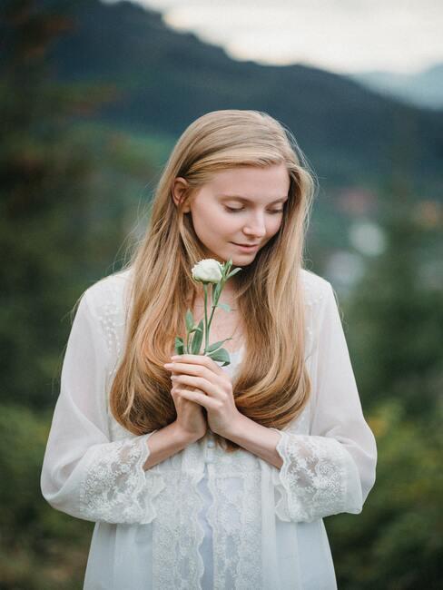 panna młoda z delikatnym makijażem z białym kwiatkiem w dłoni