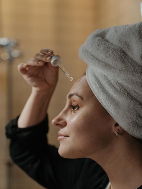 Kobieta z białym ręcznikiem na twarzy nakładająca sobie serum na twarz