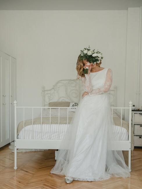 panna młoda przed ślubem oparta o łóżko z białą ramą zasłaniająca się bukietem
