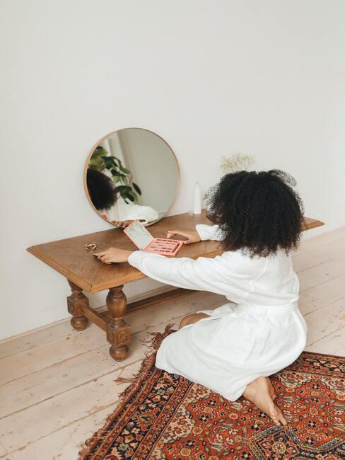 kobieta w białym szlafroku robiąca makijaż ślubny