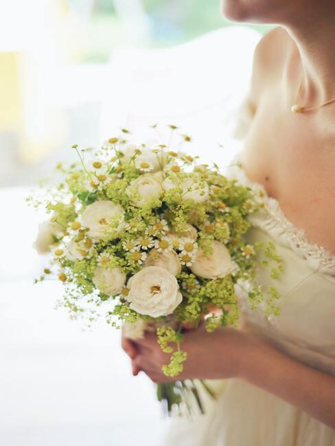 bukiet ślubny z białych i zielonych kwiatów trzymany przez Pannę młodą