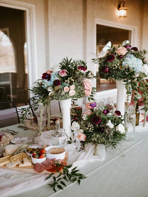 stół weselny przyozdobionymi kwiatami w kolorach różu i czerwieni w białych wazonach