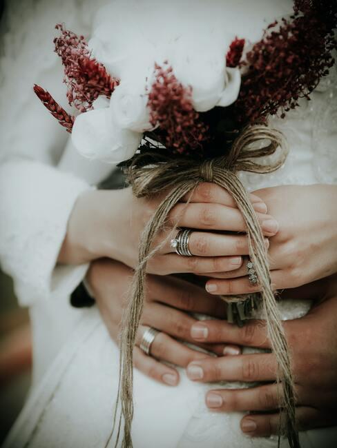 splecione ręce młodej pary na bukiecie ślubnym