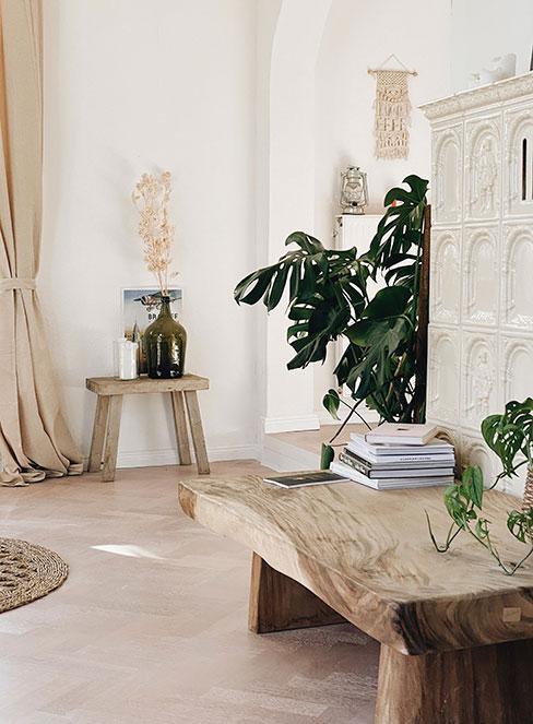 jasny beżowy przedpokój z ławkami z naturalnego drewna i piecem kaflowym w stylu rustykalnym