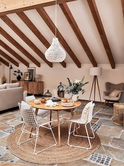 jasna jadalnia z okrągłym stołem w drewnianym domu z belkami w stylu rustykalnym