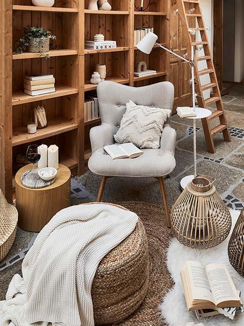 kącik do czytania z jasnoszarym fotelem uszakiem przy drewnianej biblioteczce w rustykalnym salonie