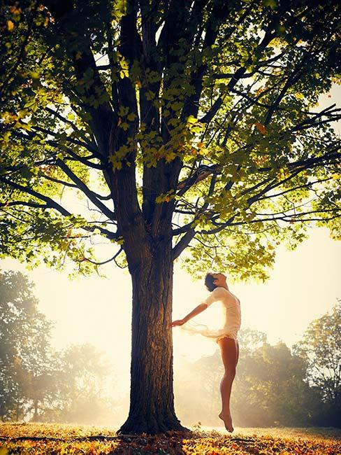 młoda kobieta tańcząca latem pod zielonym drzewem