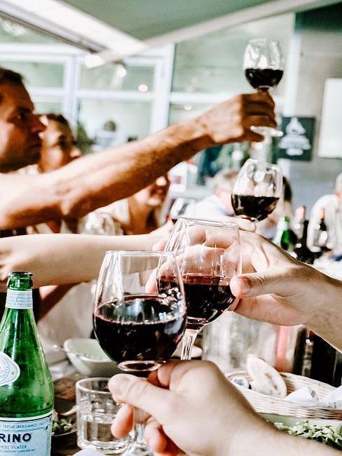 toast winem czerwonym podczas kolacji w dużej grupie