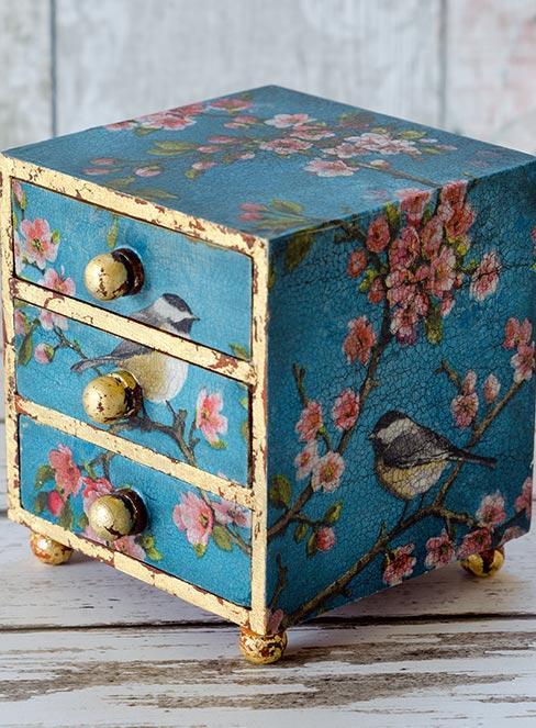 mała niebieska szkatułka z szufladami z kwiatami wiśni udekorowana techniką decoupage