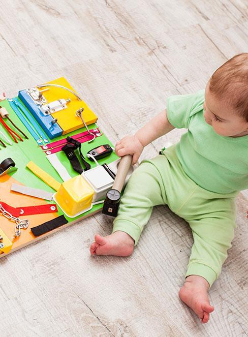 niemowlak siądzący na podłodze obok tablicy manipulacyjnej