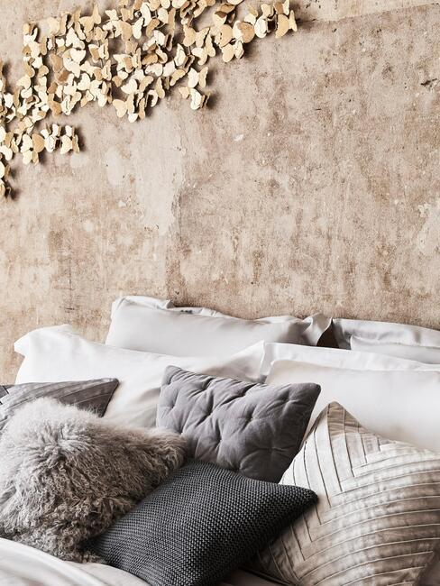sypialnia z obnażoną betonową ścianą na której widnieje złota dekoracja w kształcie motyli