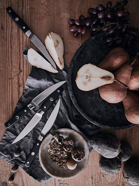 pokrojone gruszki na czarnym talerzu który stoi na drewnianym stole