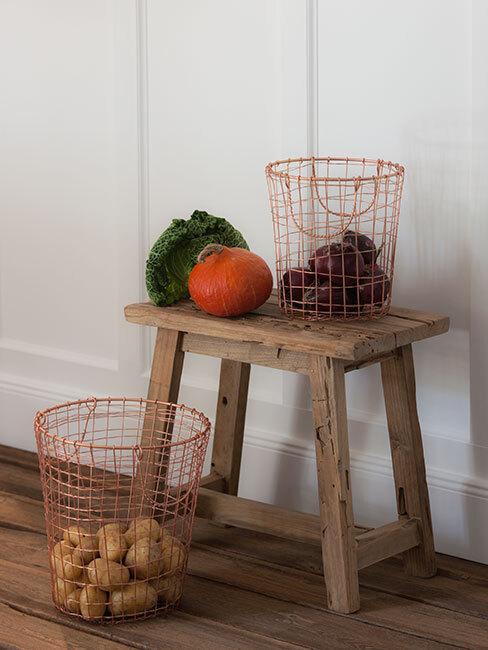 jesienne owoce i warzywa na drewnianym stołeczku, obok kosz z ziemniakami