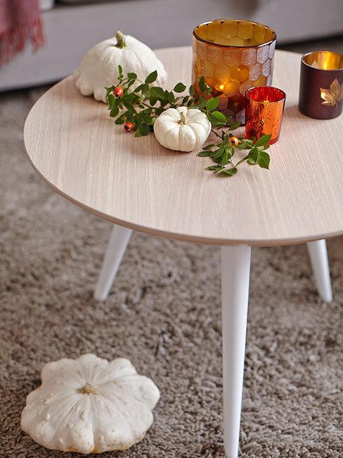 jasny stół na którym stoją małe dynie zielona gałązka i świeczki
