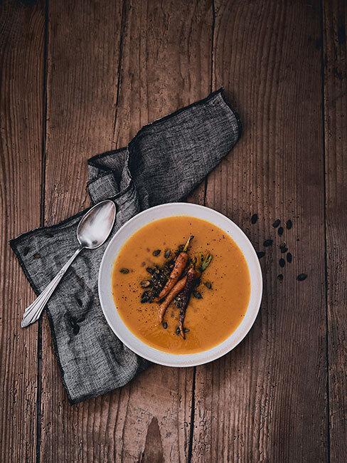 zupa krem z dyni na drewnianym stole