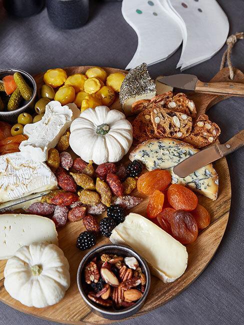 stół pełny jesiennych darów, suszone owoce, dynie, i sery