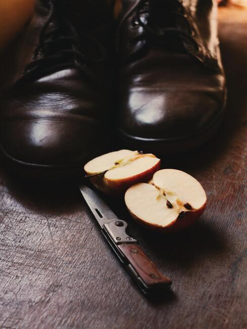 pokrojone jabłko przy ciemnych butach i nożyku do obierania
