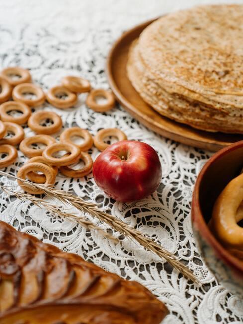 jesienne owoce: naleśniki na stole przywdzianym obrusem, obok jabłka