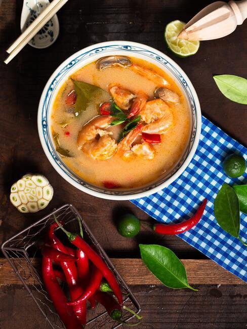 zupa w miseczce z jesiennych warzyw i krewetek w otoczeniu rozrzuconych papryczek chili