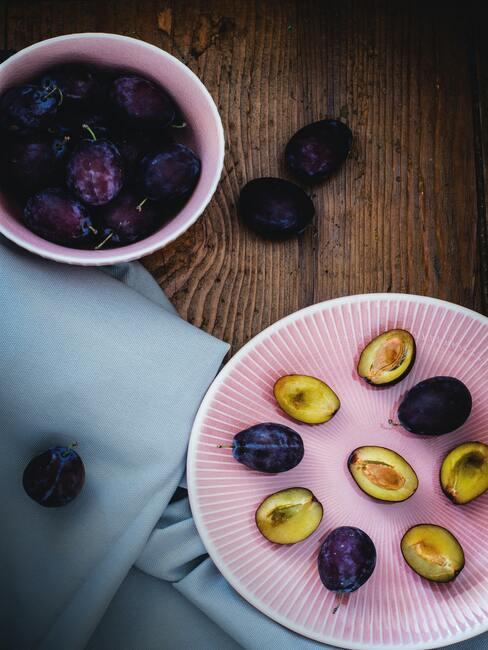 jesienne owoce: pokrojone śliwki na różowym talerzu