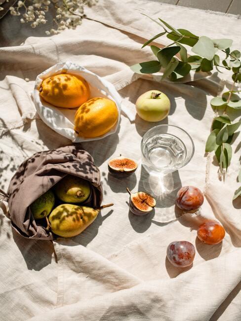 jesienne owoce na białym obrusie w promieniach słońca: gruszki jabłka, pigwa