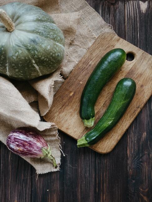 Cukinia na drewnianej desce, obok cielona dynia i inne warzywa