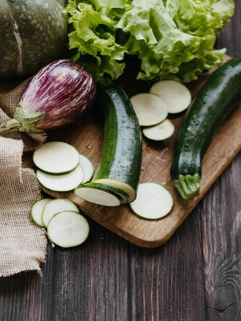pokrojona cukinia na drewnianej desce, obok sałata i inne warzywa