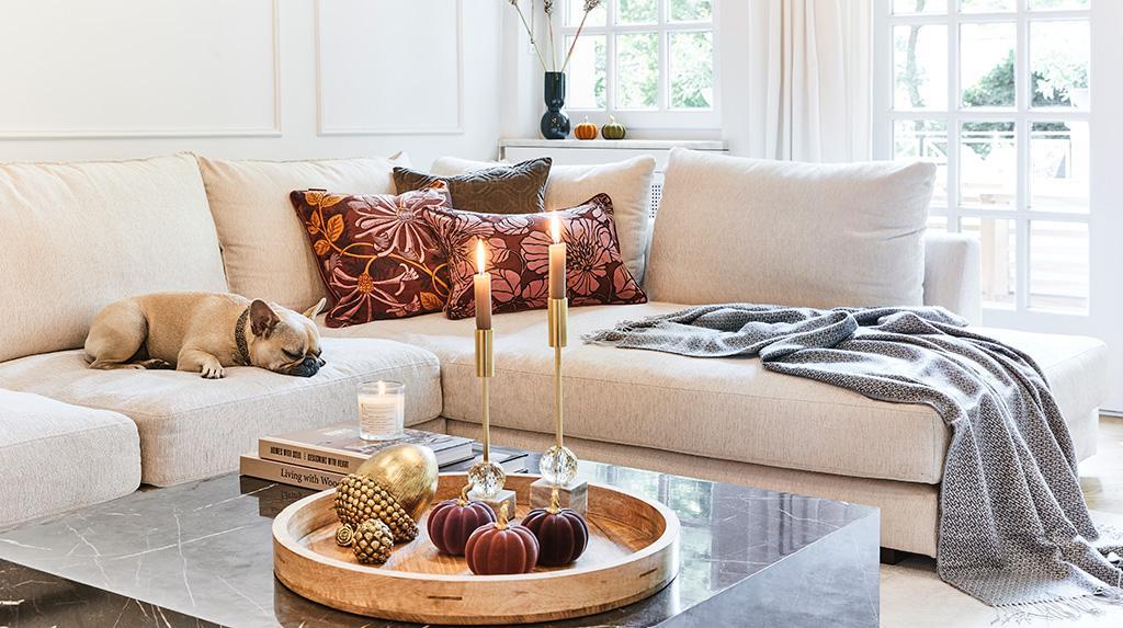 jesienne tapety: Beżowa kanapa z ozdobnymi poduszkami w różowe kwiaty, na stole taca z owocami i zapalonymi świecami