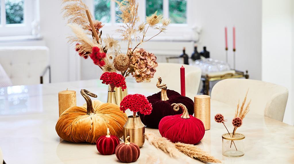 stół ozdobiony na jesień przy pomocy dekoracji w kształcie dyni i bukietu suchych traw