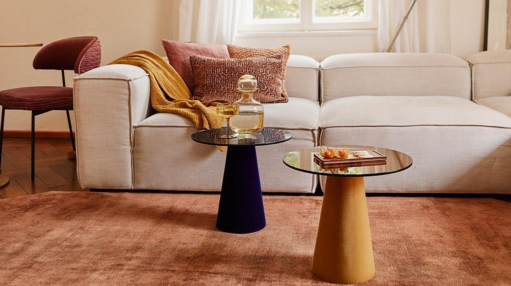 biała kanapa z dodatkami w jesiennych kolorach, obok dwa stoliki, czarny i złoty