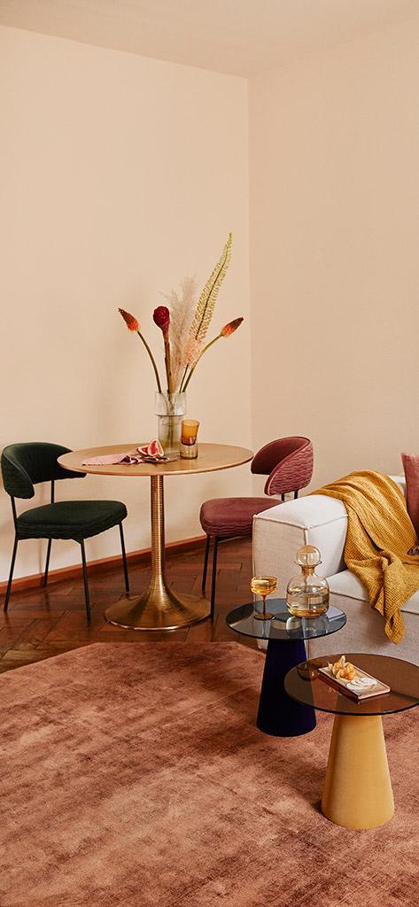 wnętrze w jesiennych kolorach, zielone i różowe krzesło przy drewnianym stoliku wraz z jesiennymi dodatkami