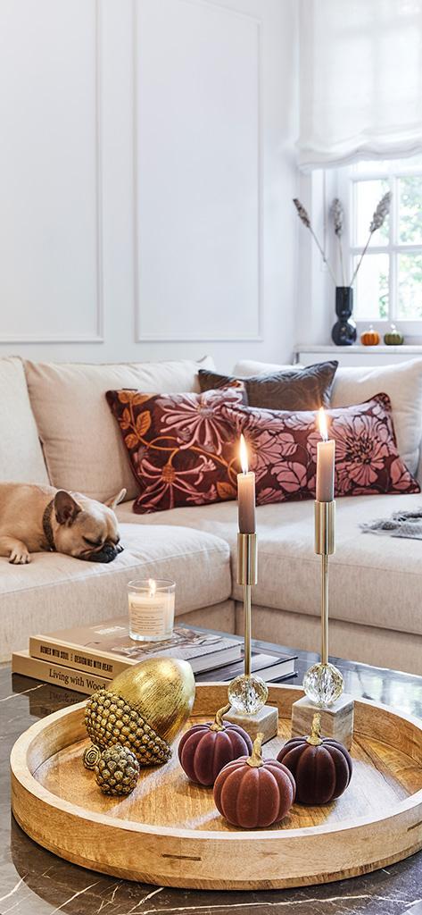 Wnętrze udekorowane na jesień: beżowa kanapa z poduszkami w kolorach jesien przed którą stoi stół z zapalonymi świeczkami