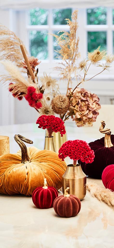 jesienny bukiet kwiatów w złotym wazonie i dodatkami w kształcie dyni na stole