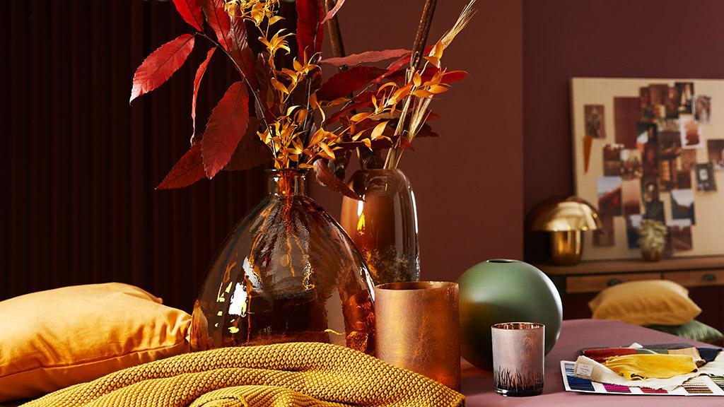 jesienne tapety: czerwone liście w wazonie z ciemnego szkła na stole