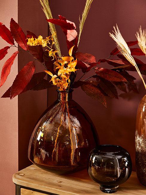 wazon w kolorze bursztynowym z jesiennymi liśćmi na komodzie