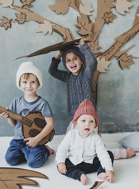 dzieci z tekturowymi instrumentami na tle jesiennego drzewa z tektury