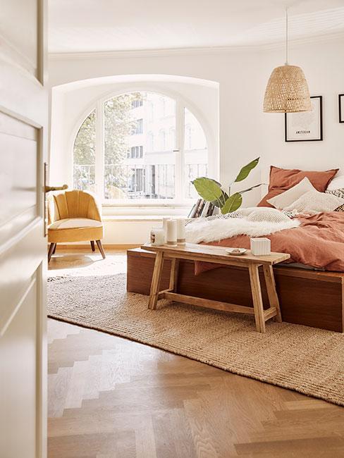 sypialnia w stylu boho z pościelą w kolorze terakoty i żółtym fotelem