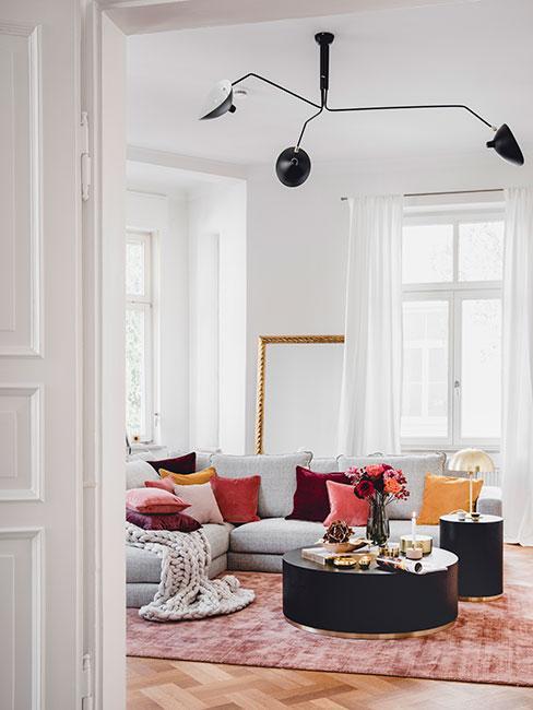duży salon w kamienicy z szarą sofą narożną i poduszkami w jesiennych kolorach